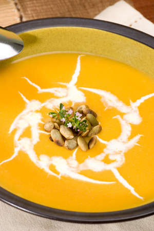 Bowl of hot delicious pumpkin soup garnished with cream, roasted pumpkin seeds and fresh thyme Stock Photo - 3534856