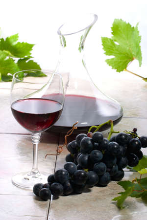 decanter: Glass of red wine, decanter and fresh cut black wine grape bunch.