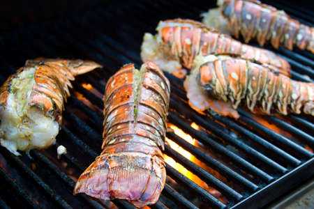 Closeup of delicious juicy lobster tails is grilling on open fire
