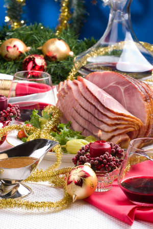 loin: Holiday table setting with delicious whole baked sliced ham, marinated peppers, cherry tomatos, vegetable salad and glasses of red wine. Christmas decoration, candles, ornaments arround.