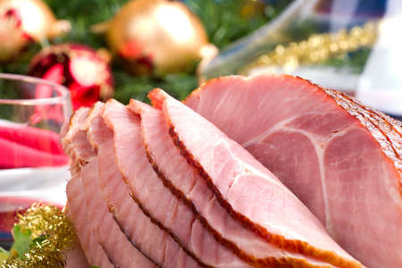 Holiday table setting with delicious whole baked sliced ham, vegetable salad and glasses of red wine. Christmas decoration, candles, ornaments arround.