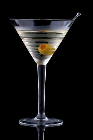 chilled: Classical martini in chilled glass over black background on reflection surface, garnished with olive. Most popular cocktails series. Stock Photo