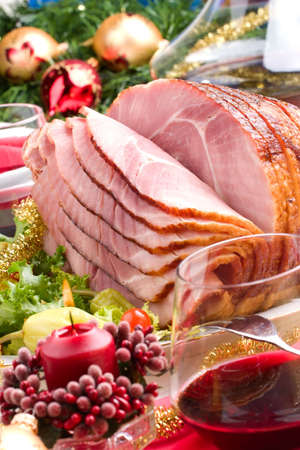 Holiday table setting with delicious whole baked sliced ham, marinated peppers, cherry tomatoes, vegetable salad and glasses of red wine. Christmas decoration, candles, ornaments around. Stock fotó