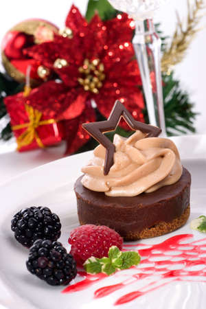 Closeup of delicious chocolate cheesecake served with fresh raspberry, blackberry and mint. Christmas ornament out of focus in background photo