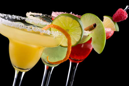 beverages: Three Margaritas - apple, orange and raspberry - in chilled glasses over black background, garnished with slice of green apple, limes, orange twist, raspberry and cinnamon stick. Most popular cocktails series. Stock Photo