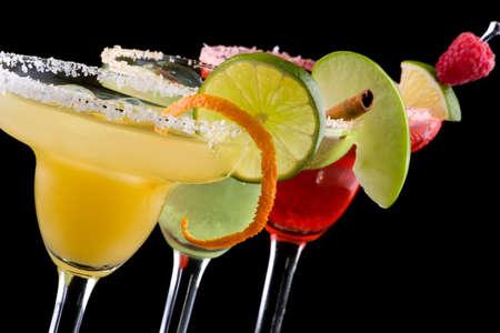 margarita cocktail: Tre Margaritas - mela, arancio e lampone - in refrigerate bicchieri su sfondo nero, decorato con fetta di mela verde, tigli, torsione arancio, lampone e cannella bastone. La maggior parte dei cocktail popolare serie. Archivio Fotografico
