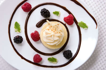 baked treat: Delicious Vanilla Bean Cheesecake served with fresh raspberries, blackberries and mint. Stock Photo