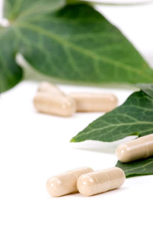 Closeup of herbal supplement pills and fresh ivy leaves best suited for alternative medicine ads. Shallow DOF. Zdjęcie Seryjne