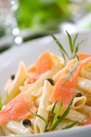 Closeup of plate of Smoked Salmon Penne (tube-shaped pasta) with cappers, tarragon and cheese creamy sauce. Caesar salad and glass of white wine out of focus. Shallow DOF Stock Photo - 3769589