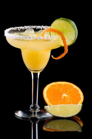 chilled: Orange Margarita in chilled glass over black background on reflection surface, garnished with fresh lime and orange. Most popular cocktails series. Stock Photo