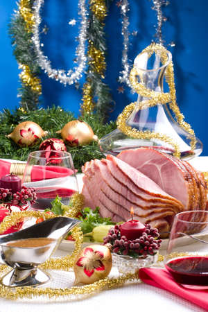 Holiday table setting with delicious whole baked sliced ham, marinated peppers, cherry tomatoes, vegetable salad and glasses of red wine. Christmas decoration, candles, ornaments around. photo