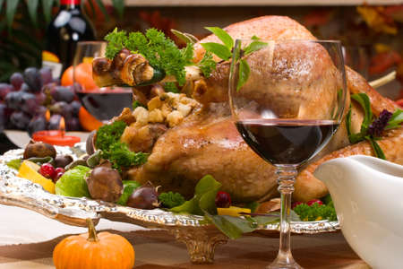 garnished: Garnished roasted turkey on holiday decorated table with pumpkins and glasses of red wine