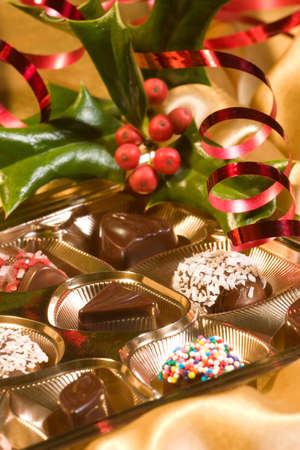 Assorted chocolate candy in a box with Christmas decoration. Shallow DOF. photo