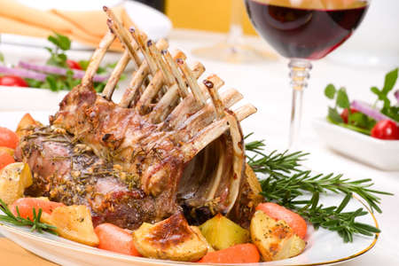 Rack of Lamb (ribs) with Rosemary garlic dressing, garnished with baby carrots, potatoes and rosemary sprigs. Dinner settings. Stock Photo - 3853349