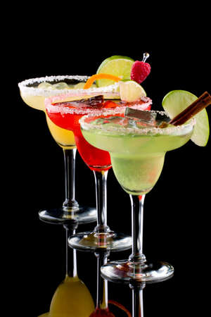 Three Margaritas - apple, orange and raspberry - in chilled glasses over black background, garnished with slice of green apple, limes, orange twist, raspberry and cinnamon stick. Most popular cocktails series. Stock Photo