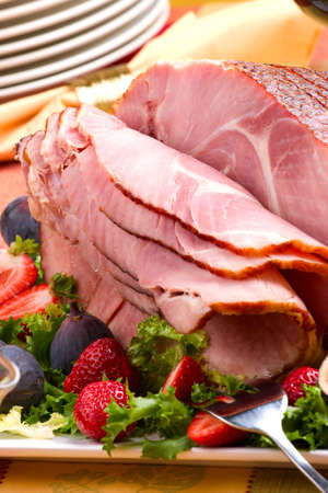 Closeup of delicious whole baked sliced ham with fresh strawberries and figs on holiday table. photo