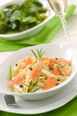 saumon fum�: Penne au saumon fum� (p�tes en forme de tube) avec des c�pres, l'estragon et sauce au fromage cr�meux. Salade C�sar et un verre de vin blanc hors foyer. Shallow DOF
