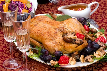 Garnished roasted duck on Christmas decorated table photo