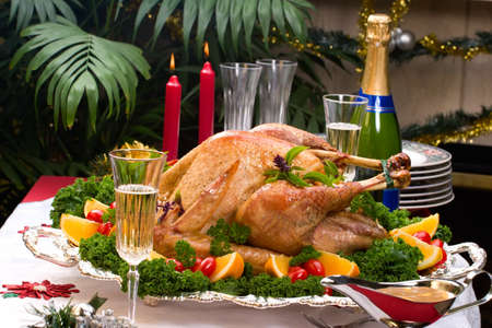 Garnished roasted turkey on Christmas decorated table with candles and flutes of champagne photo