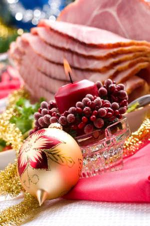 ham: Holiday tabel met heerlijke hele gebakken gesneden ham, gemarineerde paprika, cherry tomaten, groente salade en glazen rode wijn. Kerstversiering, kaarsen, ornamenten rond. Stockfoto