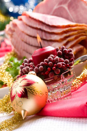 Holiday table setting with delicious whole baked sliced ham, marinated peppers, cherry tomatoes, vegetable salad and glasses of red wine. Christmas decoration, candles, ornaments around. Stock Photo