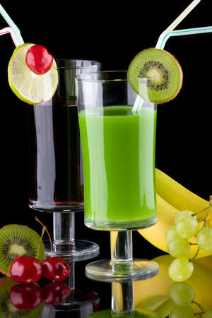 Two glasses of organic juice made from fresh fruits and surrounded by fresh ones. Series about organic and healthy drinks. photo
