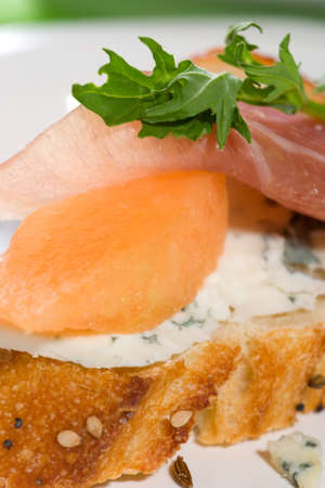 Closeup of delicious Prosciutto canape-sandwiche made from cantaloup melon, blue cheese, Prosciutto ham and salad.  photo
