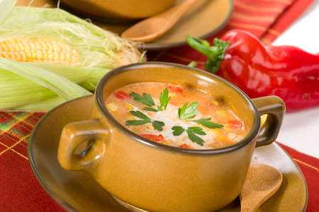 chowder: Bowl of hot delicious corn and red chilli chowder garnished with cream and fresh parsley
