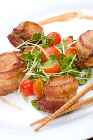 crusted: Closeup of Ginger Soy Scallops wrapped by bacon garnished with fresh cherry tomatoes and daikon sprouts.