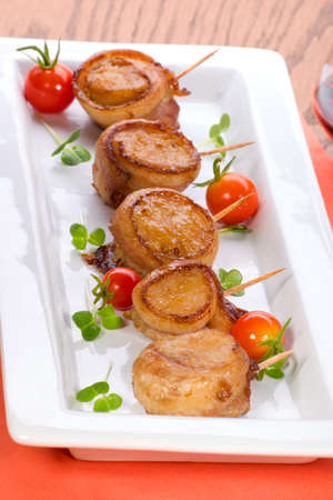 Ginger Soy Scallops wrapped by bacon garnished with fresh cherry tomatoes and daikon sprouts.