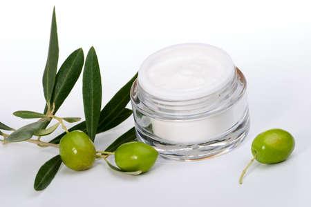 cremas faciales: Closeup del tarro de crema facial hidratante y ramita con aceitunas verdes.