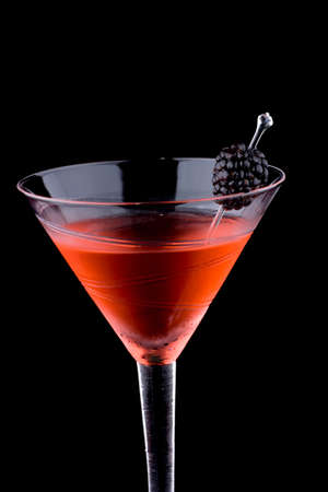 Martini in chilled glass over black background. Red color, made with blackberry liqueur and garnished with freah blackberry. Most popular cocktails series. Stock Photo - 4139572