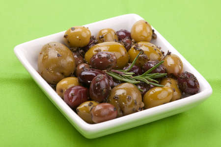 Closeup of small plate full of olives, marinated with herbs on green table-cloth Stock Photo - 4152682