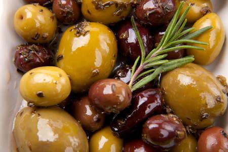 Extreme close-up van kleine plaat vol olijven, gemarineerd met kruiden