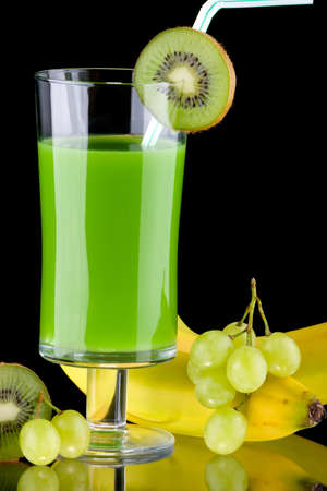Organic juice made from kiwi, green grapes and bananas surrounded by fresh fruits. Series about organic and healthy drinks. photo