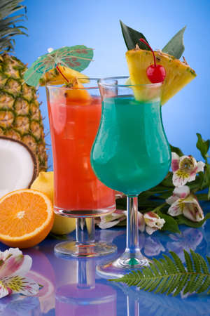 Blue Hawaiian and Hurricane cocktails surrounded by tropical fruits. Most popular cocktails series. photo