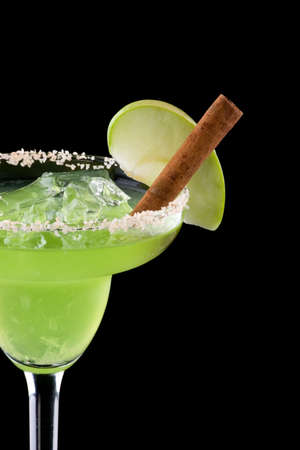 chilled: Apple Margarita in chilled glass over black background on reflection surface, garnished slice of green apple and cinnamon stick. Most popular cocktails series. Stock Photo