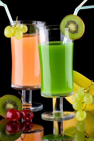 Two glasses of organic juice made from fresh fruits and surrounded by fresh ones. Series about organic and healthy drinks. Banco de Imagens