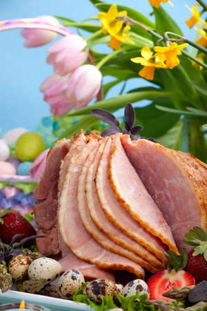 Honey ham on Easter table with quail eggs, tulips and decoration