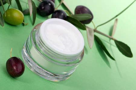 cremas faciales: Closeup del tarro de crema facial hidratante y negro ramita con aceitunas. Foto de archivo
