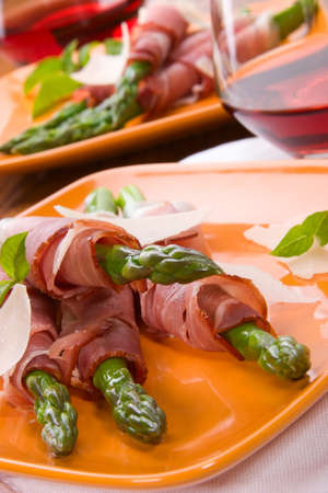 Crispy asparagus wrapped in fresh prosciutto and parmesan cheese.  Reklamní fotografie