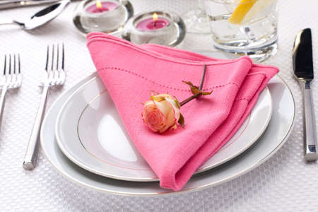 Romantic table settings. Arrangments with fresh roses and scented candles photo