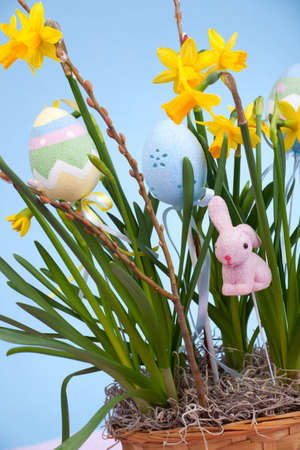 Basket of daffodils and easter eggs photo