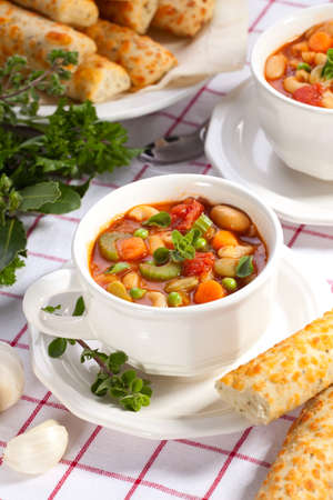 minestrone: Two bowls of hot fresh Minestrone soup and cheese garlic breadsticks Stock Photo