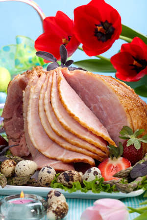 Honey ham on Easter table with quail eggs, tulips and decoration photo