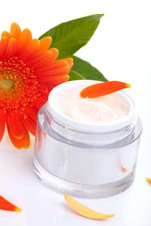 cremas faciales: Closeup del tarro de crema facial hidratante rodeado de flores de gerbera naranja