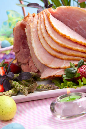 Honey ham on Easter table with eggs, flowers and decoration photo