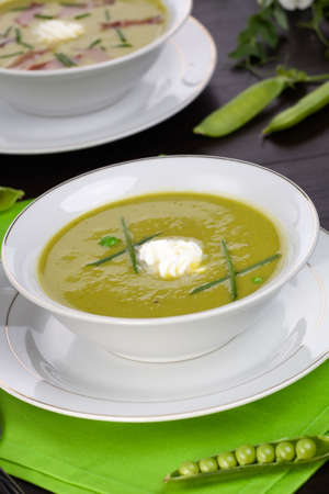 Bowls of pea soup with prosciutto garnished with chives. Sprig of flowering pea and cracked pea pods. photo