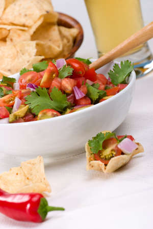 Bowl with fresh cherry tomatoes and avocado salsa. Corn chips and beer. Very shallow DOF on salsa. Imagens