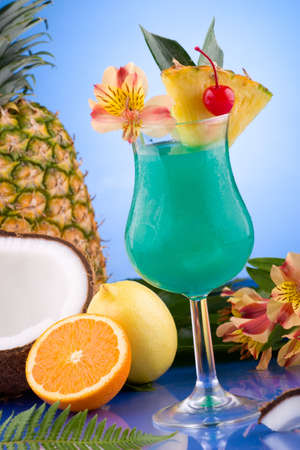 Blue Hawaiian cocktail surrounded by tropical fruits. Rum, pineapple juice, coconut milk and blue curacao garnished with slice of pineapple and maraschino cherry. Most popular cocktails series. photo
